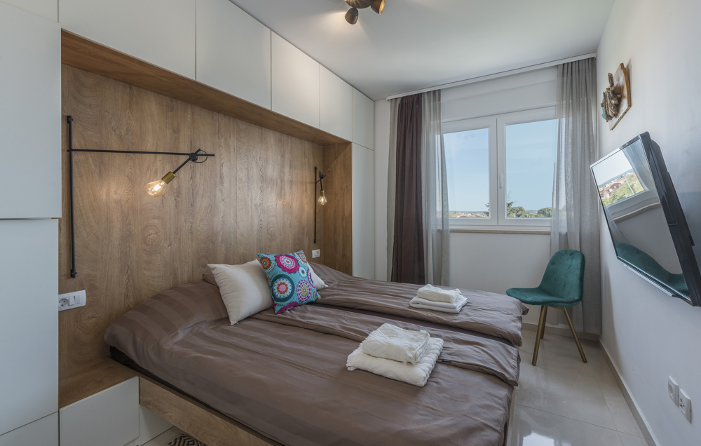 One bedroom with wall unit, double bed and window - buy an apartment in Croatia.