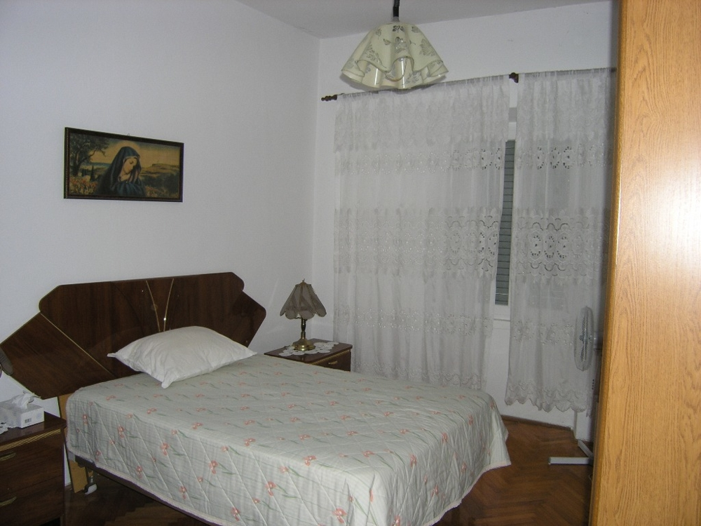 One bedroom with double bed and window of property H1275 in North Dalmatia.