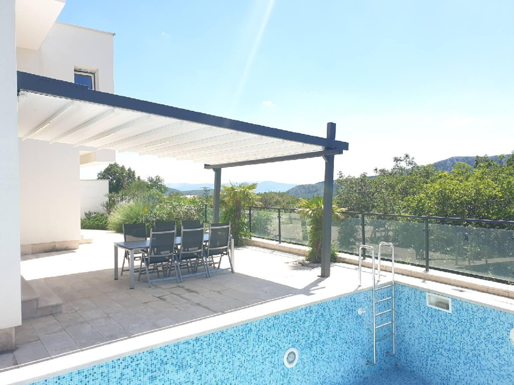 Swimming pool and terrace with a view of the Mediterranean mountains and the sea.