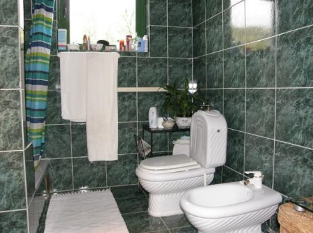 A tiled bathroom with toilet and shower