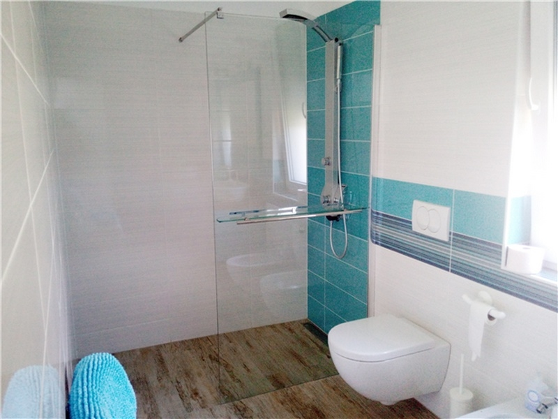 Turquoise bathroom with walk-in shower.