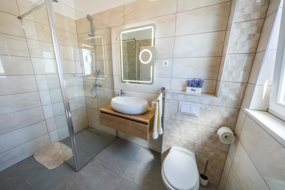 A bathroom with walk-in shower and toilet of property H1467.