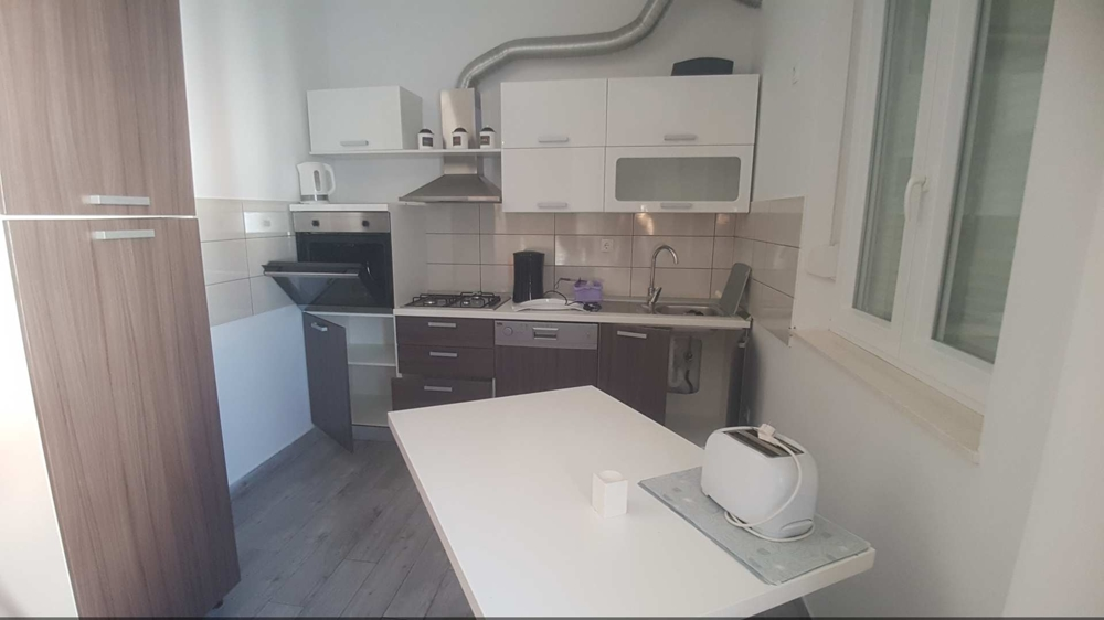 View of a kitchen with all the necessary appliances and dining table in Croatia.