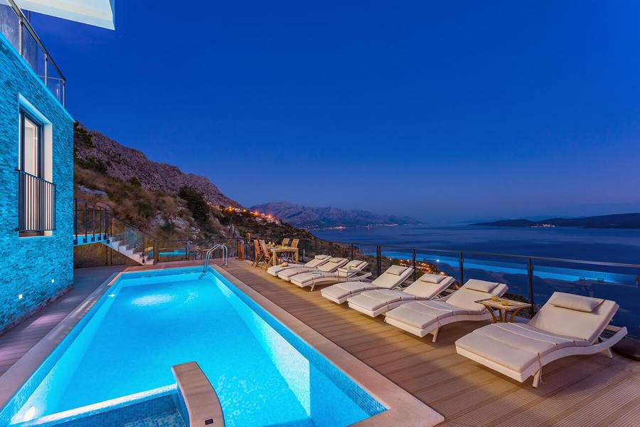 Illuminated swimming pool and sea view - taken from the terrace of property H1513.