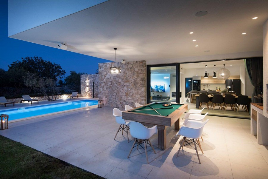 View of the swimming pool, pool table and the living room of the property.