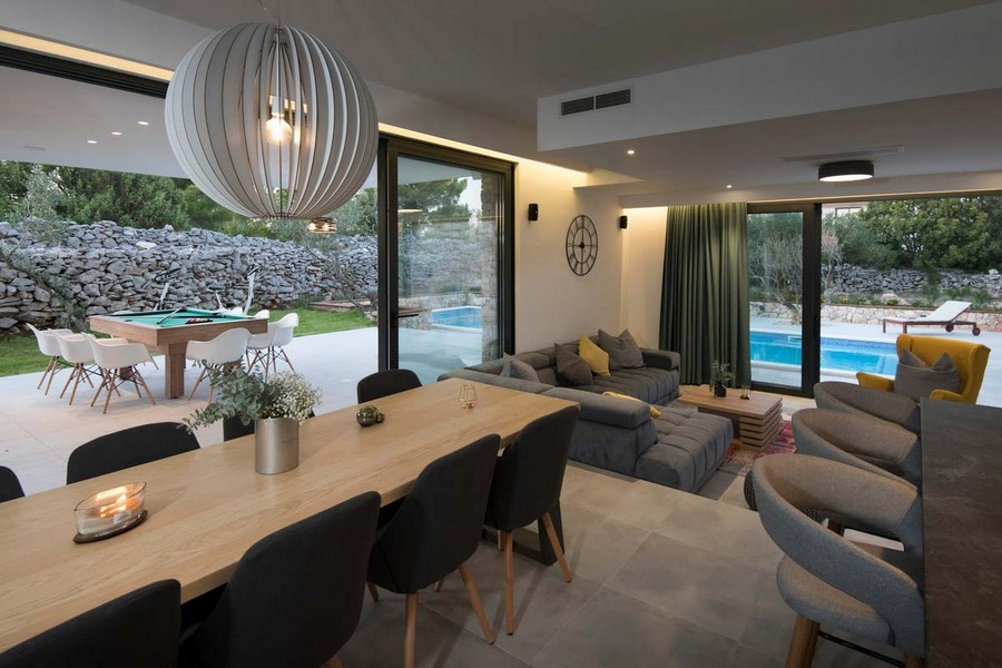 View from the kitchen to the dining area with exit to the terrace with large windows and a view of the swimming pool and the garden.