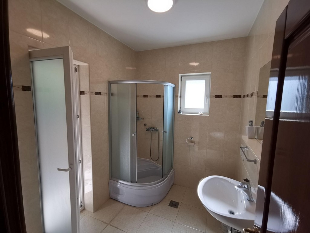 A bathroom of the property H1557 with shower, toilet and window in the Kvaner Bay.