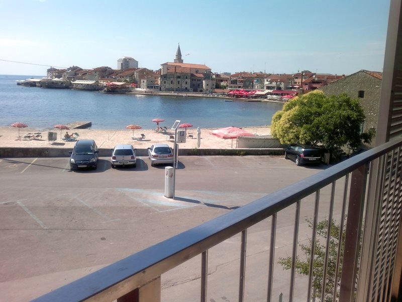 The beautiful view on the sea and the city bay from the balcony of the apartment for sale in Umag, Istria